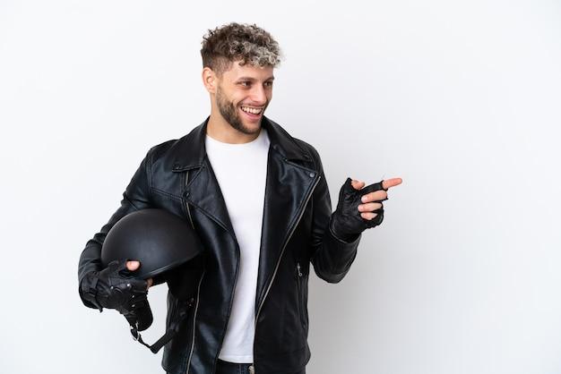 Молодой человек в мотоциклетном шлеме на белом фоне, указывая пальцем в сторону и представляя продукт