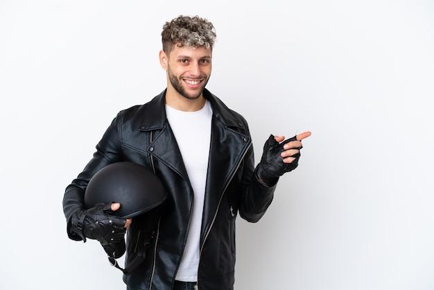 Молодой человек в мотоциклетном шлеме на белом фоне, указывая пальцем в сторону