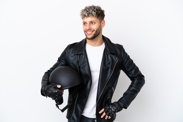 Молодой человек в мотоциклетном шлеме на белом фоне позирует с руками на бедрах и улыбается