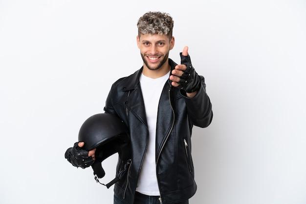 Молодой человек в мотоциклетном шлеме на белом фоне, пожимая руку для заключения хорошей сделки