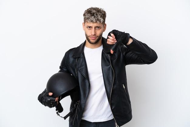 Молодой человек в мотоциклетном шлеме на белом фоне показывает большой палец вниз с отрицательным выражением лица