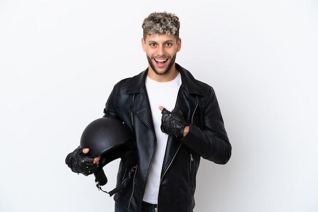 驚きの表情で白い背景に分離されたオートバイのヘルメットを持つ若い男