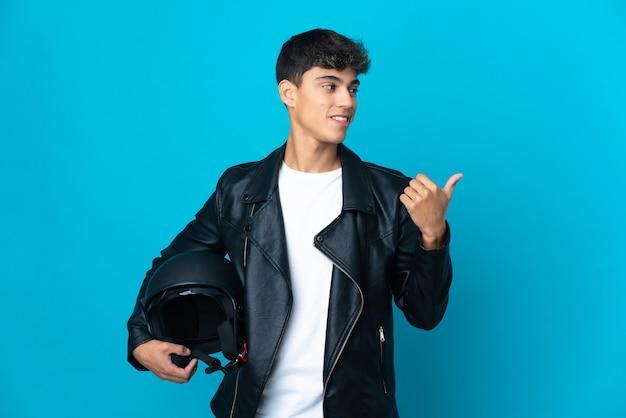 製品を提示する側を指している青の上のオートバイのヘルメットを持つ若い男