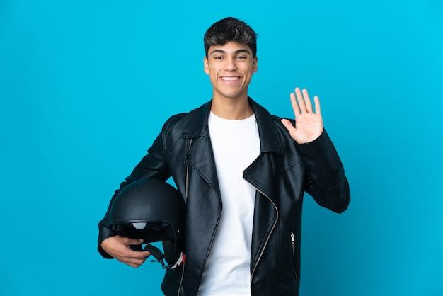 幸せな表情で手で敬礼する孤立した青い背景の上のオートバイのヘルメットを持つ若い男
