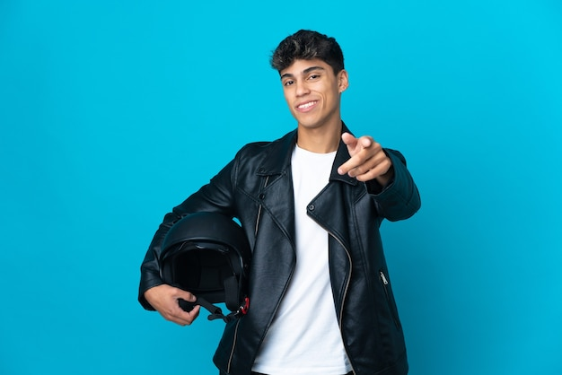 幸せな表情で正面を指している孤立した青い壁の上のオートバイのヘルメットを持つ若い男