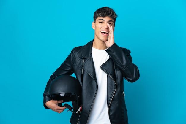 口を大きく開いて叫んで孤立した青い壁の上のオートバイのヘルメットを持つ若い男