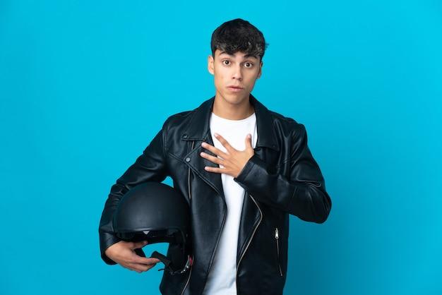 孤立した青い壁にオートバイのヘルメットをかぶった若い男は、右を見ながら驚いてショックを受けました