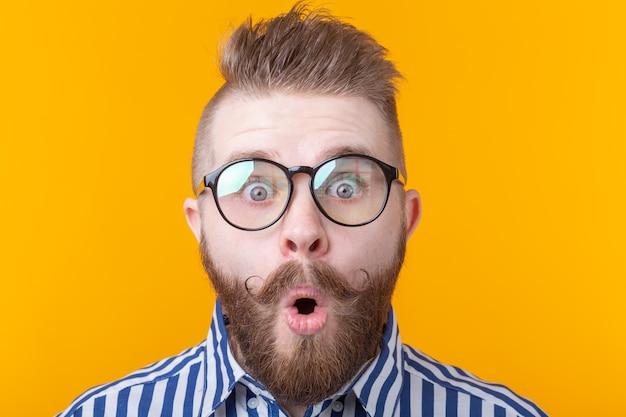 콧수염과 수염을 가진 젊은 남자가 놀람에 입을 둥글게했습니다.