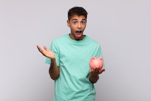 幸せ、興奮、驚き、ショック、笑顔、信じられないほどの何かに驚いた貯金箱を持つ若い男