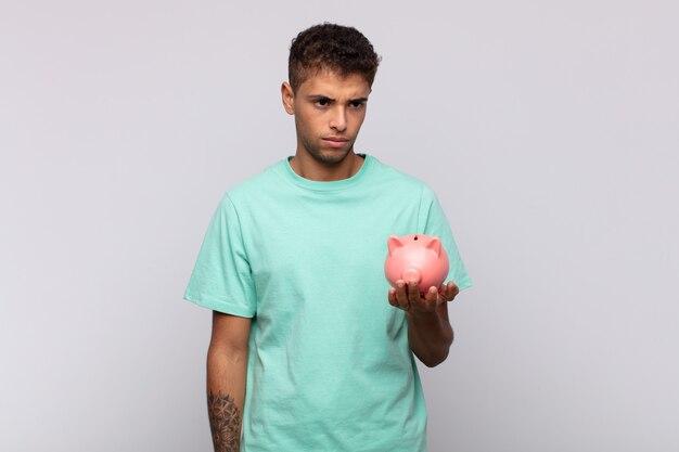 Молодой человек с копилкой грустит, расстроен или зол и смотрит в сторону с отрицательным отношением, хмурясь в знак несогласия
