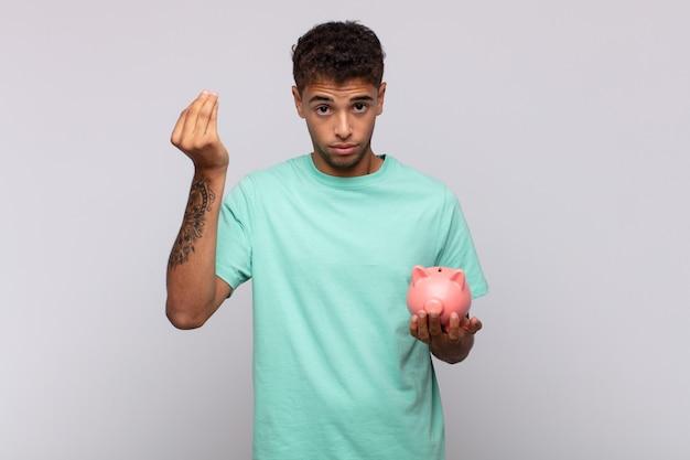 貯金箱を持って、借金を返済するように言って、お金やお金のジェスチャーをしている若い男!