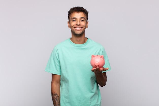 돼지 저금통을 가진 청년은 엉덩이에 손을 대고 행복하게 웃고 있고 자신감 있고 긍정적이고 자랑스럽고 친절한 태도를 가지고 있습니다.