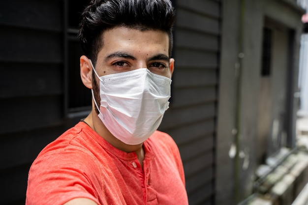 Selfieを作る防護マスクを持つ若者