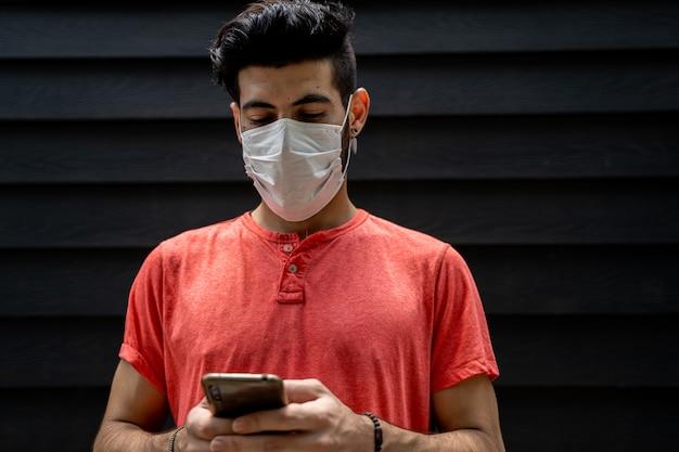 彼の携帯電話を身に着けている防護マスクを持つ若者