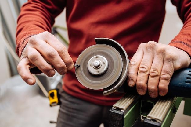 産業用工具で何かを作る赤いセーターを着た若い男