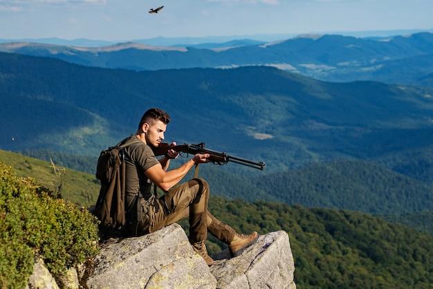 岩の上に座っているライフルを持つ若い男