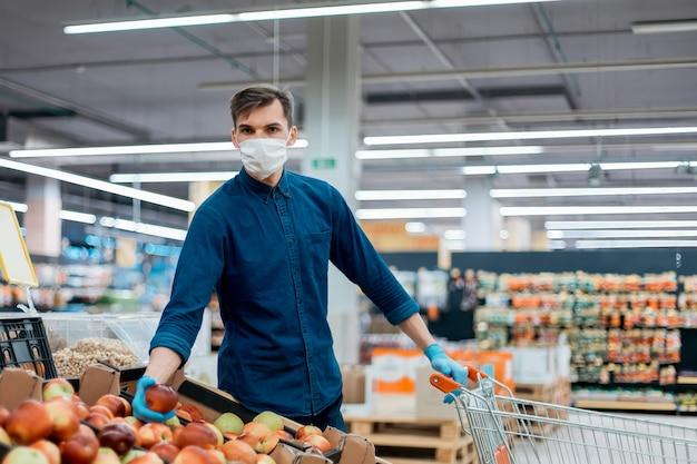 Молодой человек с тележкой, собирающей яблоки