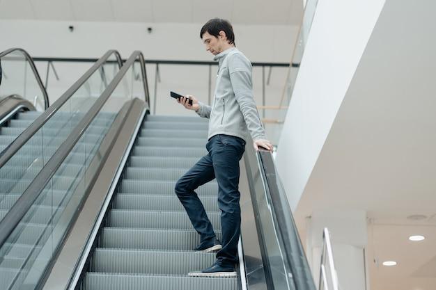 エスカレーターの近くに立っている誰かを待っているスマートフォンを持つ若い男