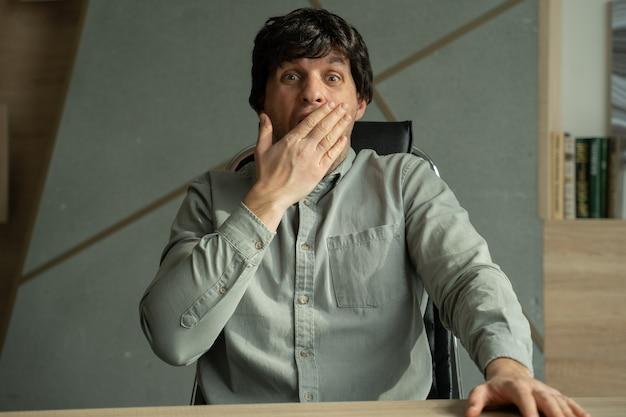 Молодой человек с удивленным выражением лица сидит в кресле в офисе