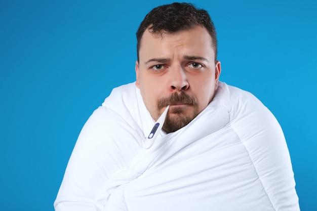 毛布に包まれた、口の中に温度計を持った若い男。