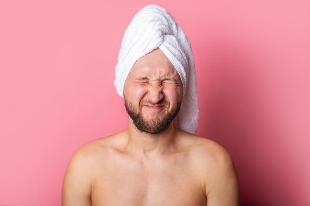 ピンクの背景に目を閉じて目を閉じて頭にタオルをかぶった若い男。