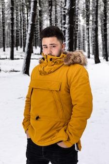 雪に覆われた森の真ん中でポーズをとって黄色のアノラックを持つ若い男