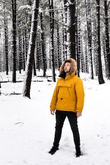 雪に覆われた森の真ん中でポーズをとって黄色のアノワクを持つ若い男