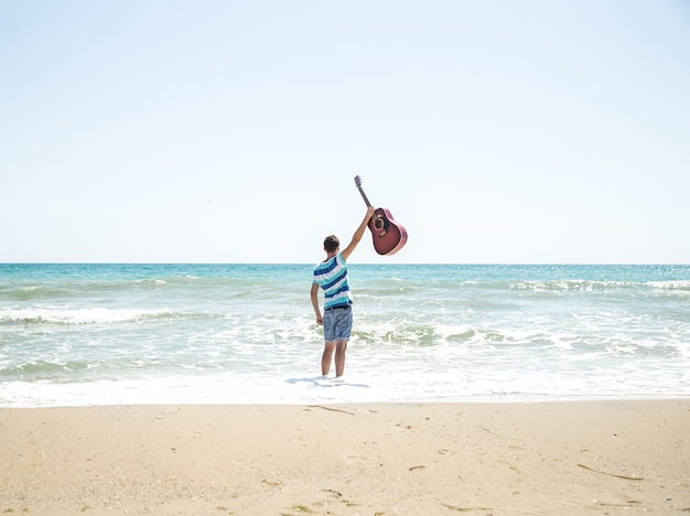 Young man with acoustic guitar on the beach, joyful emotions, the concept of leisure and music