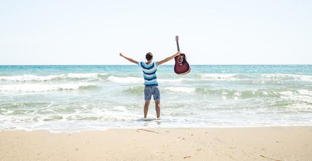 ビーチでアコースティックギターを持つ若い男
