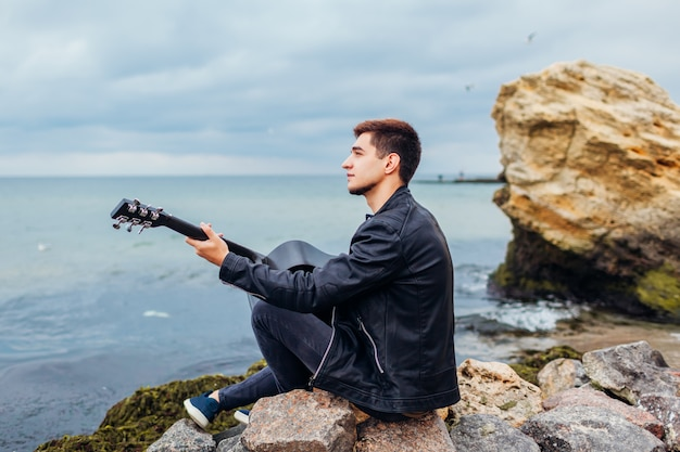 Young man with acoustic guitar playing on beach surrounded with rocks on rainy day