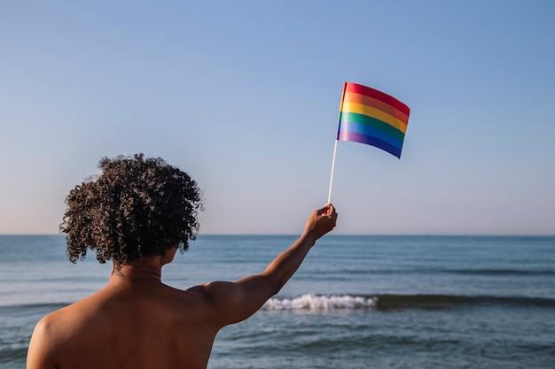 아프리카 머리를 가진 젊은 남자가 lgtbi 색상으로 페넌트를 올립니다