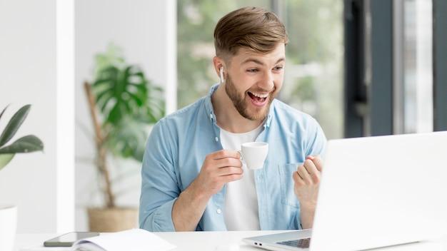 Молодой человек с airpods работает на ноутбуке