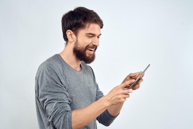 明るい背景に彼の手で電子タブレットを持つ若者