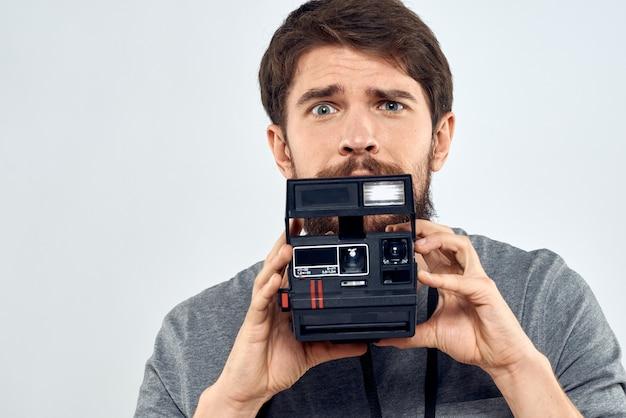 明るい背景に古いカメラを持った若い男