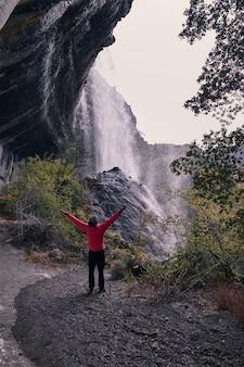 腕を持つ若い男が大きな滝の美しさを賞賛して高く保持