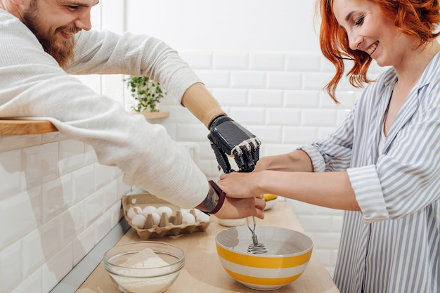 Young man with artificial limb are cooking on kitchen with his girlfriend