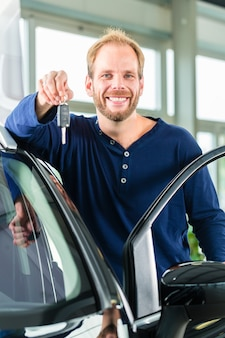 Young man with auto in car dealership