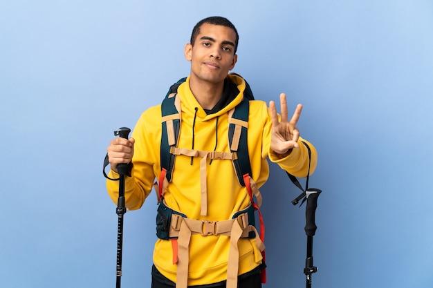 Молодой человек с рюкзаком и треккинговыми палками над изолированной стеной счастлив и считает три пальцами