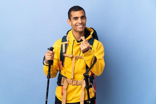 Молодой человек с рюкзаком и треккинговыми палками над изолированной стеной делает денежный жест