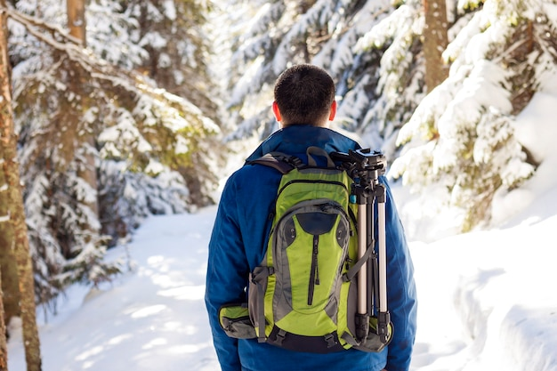 Young man with backpack hiking in winter forest