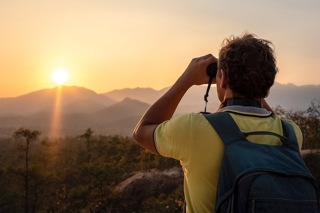 A young man with a backpack on his back looks through binoculars at the sunset at the silhouettes of the mountains.