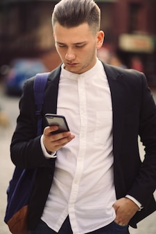 Young man with backpack holding a phone