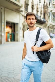 街でバックパックを持つ若い男