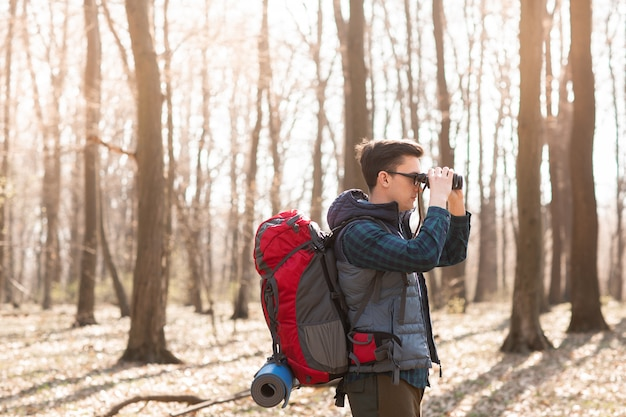 Young man with backpack looking at the binoculars, hiking in the forest