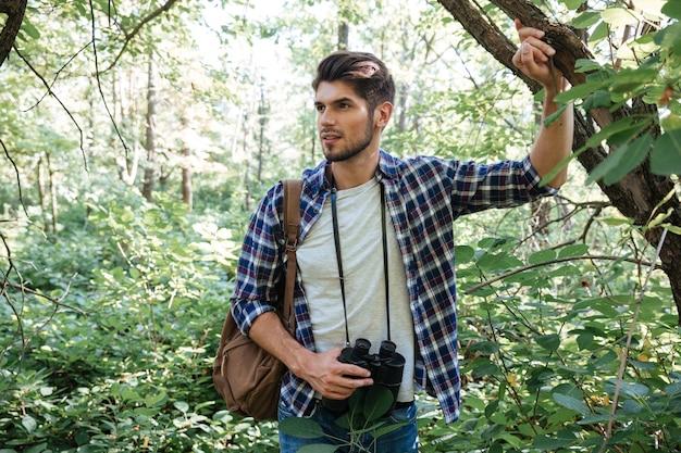 目をそらしている木の近くにバックパックを持つ若い男