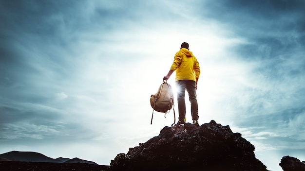 Young man with backpack standing on the top of a mountain at sunset