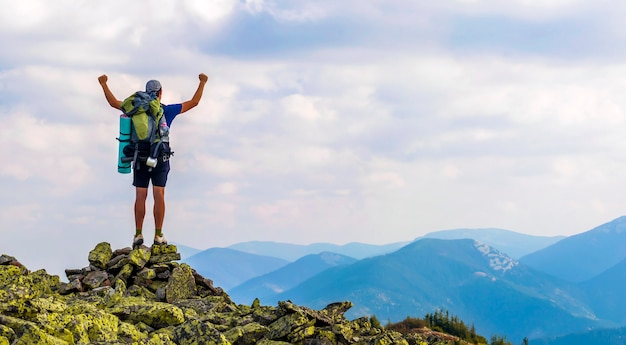 Young man with backpack standing with raised hands on top of a mountain and enjoying mountain view.
