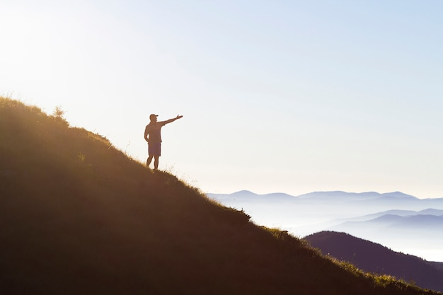 Young man with backpack standing with raised hands on top of a mountain and enjoying mountain view