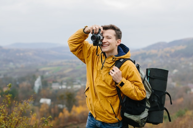 Young man with backpack takes photo on film camera in mountains