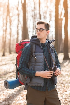 Young man with backpack and with a binocular in his hands, hiking in the forest